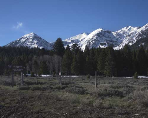 This sign points to Red Rock Mountain and Mount Jefferson, situated on the Continental Divide. This sign is visible here at the entrance to Alaska Basin in Montana. Looking east.