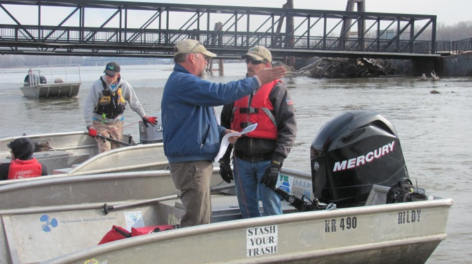 Dispatcher Jeff Barrow discussing trash locations upriver.  Scouts find the trash hot spots the day prior and mark with blue bags.