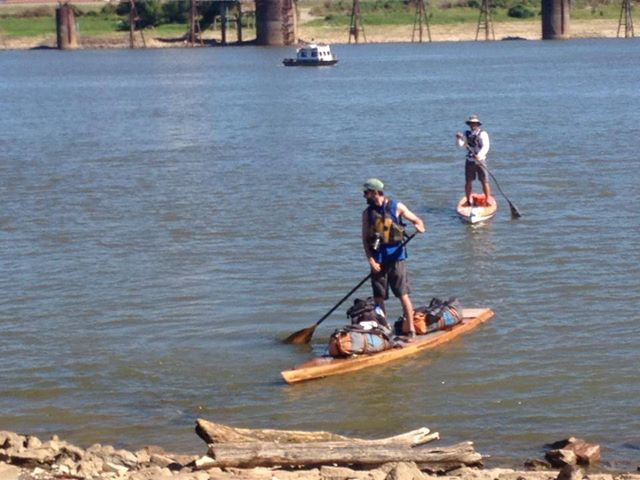 Scott landing his SUP in St. Louis after paddling 2300 miles. Shane Perrin looking on.